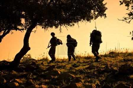 Photo pour Trois soldats de l'armée alors qu'ils patrouillaient au coucher du soleil - image libre de droit