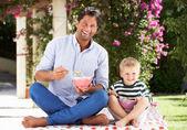 Otec a syn si pochutnávají snídaňové cereálie venku spolu