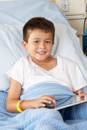 Boy Relaxing In Hospital Bed With Digital Tablet