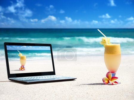 notebook on the beach and glass of fresh jucie