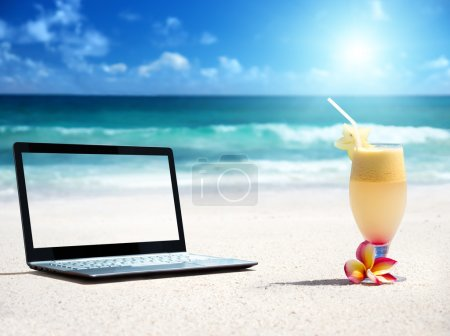 Photo for Notebook on the beach and glass of fresh jucie - Royalty Free Image