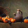 Still life with persimmons and grapes on the table...