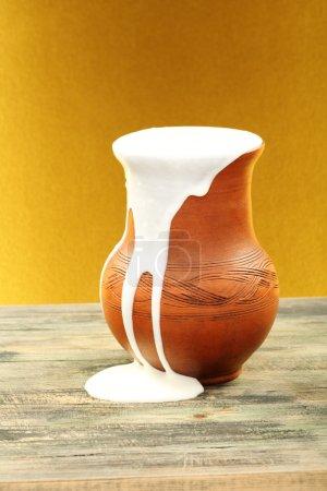 Ceramic jug overflowing cream.