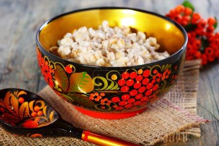 Photo pour Bouillie d'orge perlé dans un bol coloré sur une table en bois. - image libre de droit