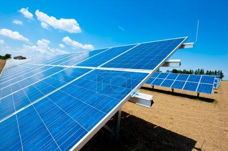 Foto de Granja de energía solar con cielo azul y algunas nubes - Imagen libre de derechos