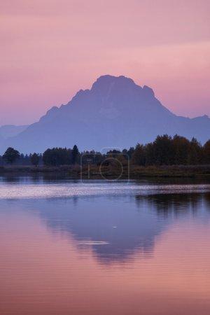Photo pour Une montagne enveloppée de brume jette un reflet sur un lac immobile juste après que le soleil se soit couché derrière, baignant le ciel d'une lueur rosée. La scène vient du virage Oxbow au parc national Grand Teton du Wyoming . - image libre de droit