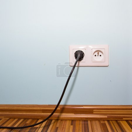 Blue room wall with electric socket and plug...