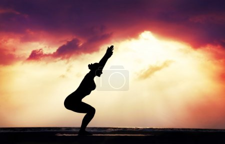 Photo for Yoga utkatasana chair pose by woman in silhouette with dramatic sunset sky background. Free space for text - Royalty Free Image