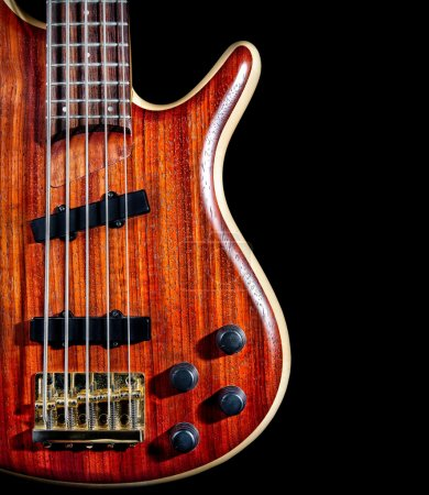 Photo for Bass guitar from red textured wood with five strings close up isolated on black background - Royalty Free Image