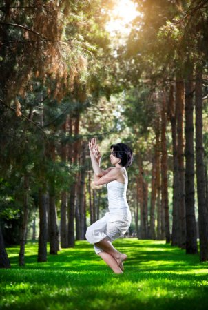 Photo for Yoga garudasana eagle pose by woman in white costume on green grass in the park around pine trees - Royalty Free Image