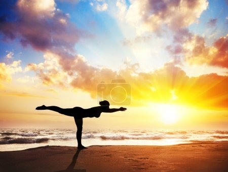 Photo for Yoga virabhadrasana III, warrior pose by woman in silhouette with sunset sky background. Free space for text - Royalty Free Image