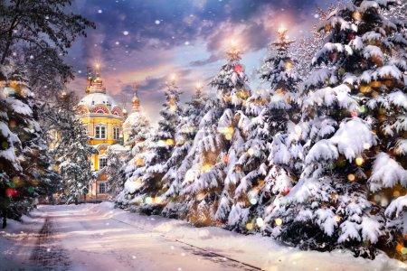 Photo pour Eglise avec des arbres de Noël illuminés en chute de neige la veille de Noël en hiver - image libre de droit