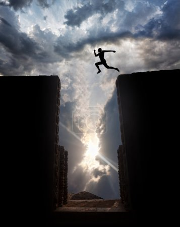 Photo for Man Silhouette jumping over the abyss at sunset cloudy sky background - Royalty Free Image