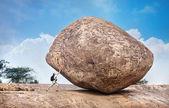 Muž tlačí velký kámen