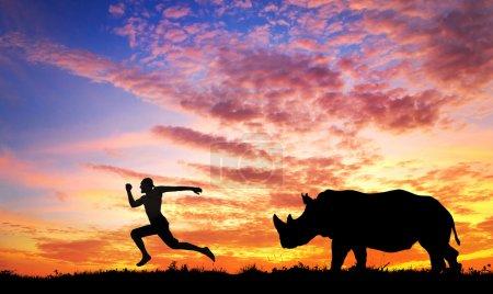 Photo pour Homme fuyant le rhinocéros au coucher du soleil en savane - image libre de droit