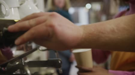 Close up of a coffee machine and female barista serving customers