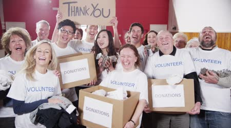Happy group of fundraisers holding donated goods and a Thank You sign