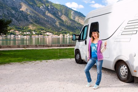 Happy young woman outside camper