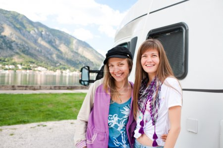 Young women in front of motorhome