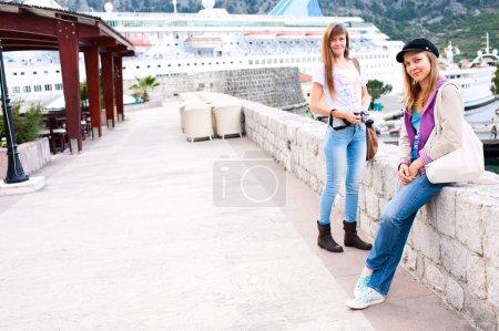 Happy tourist women on a stone pier