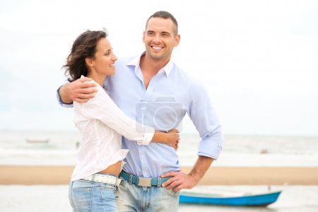 Portrait of a happy young couple having fun at the sea shore