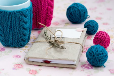 Photo for Two blue cups in blue and pink sweater with ball of yarn for knitting - Royalty Free Image