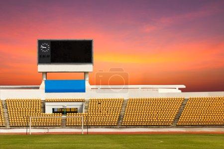 Photo pour Rangées de sièges orange sur le stade avec tableau de bord d'afficher l'horloge au-dessus d'eux - image libre de droit