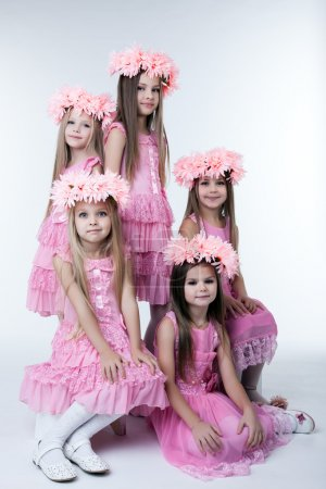 Five little girls in pink dresses and wreaths