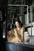 Krása ženy v zlaté šaty pózuje na baru stůl