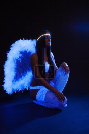 Sexy slim girl with UV makeup posing as angel