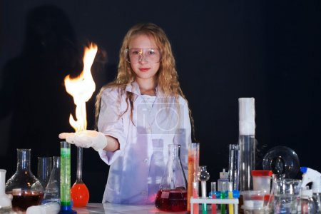 Curly girl shows science experiment in studio