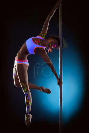 Sexy dancer with disco makeup posing on pylon
