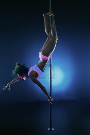 Image of athletic young girl dancing on pole