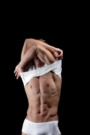 Shot of young muscular man takes off his shirt