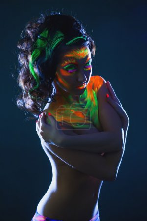 Topless girl posing with glowing UV makeup