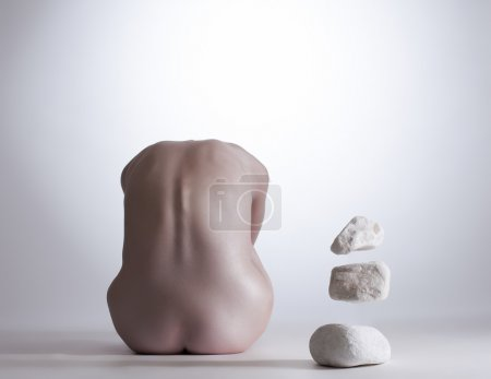 Rear view of nude girl mentally commands stones