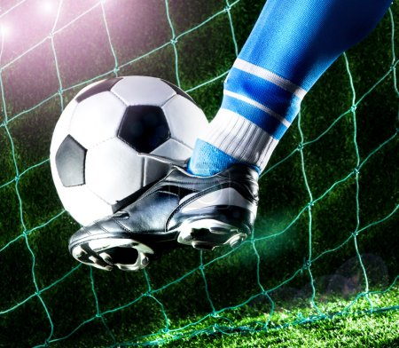 Photo for Foot kicking soccer ball on playing field with dark background - Royalty Free Image