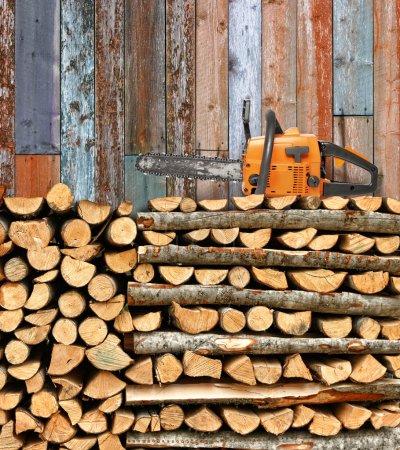 Photo pour Tas de bois de chauffage empilés et scie à chaîne contre les murs en bois altérés - image libre de droit