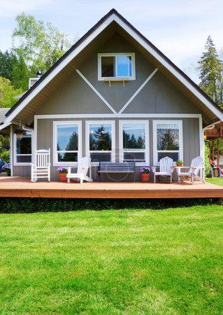 Modern American farm cottage house exterior with deck.