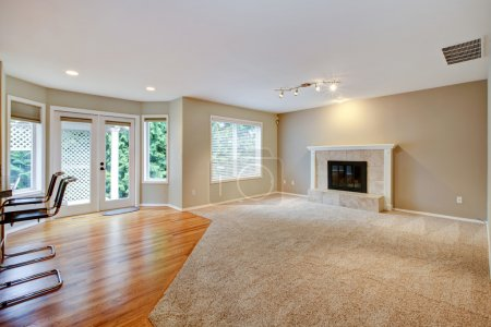 Photo for Large bright empty new living room with fireplace and beige carpet. - Royalty Free Image