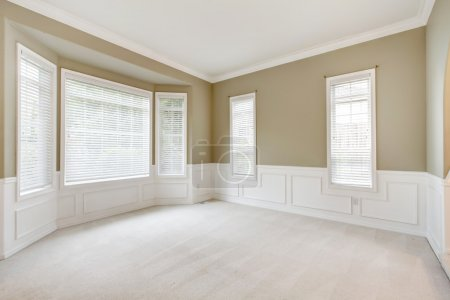 Photo for Bright lbeige arge empty room with carpet, molding and windows. - Royalty Free Image