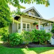 Grey small house with porch and white railings wit...