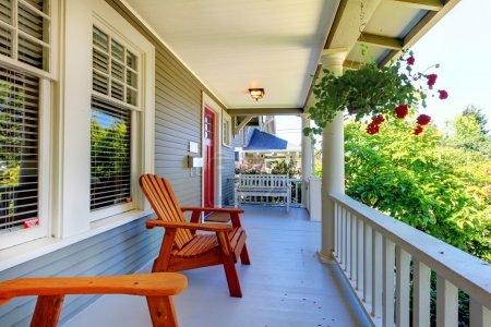 Photo pour Porche de la maison grise avec des balustrades blanches et deux fenêtres avec des fleurs - image libre de droit