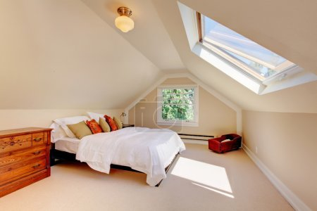 Attic modern bedroom with white bed and skylight.