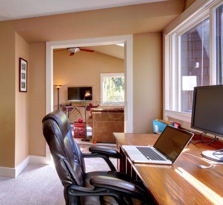 Photo pour Bureau à domicile et ordinateur et chaise avec murs bruns et TV dans le salon . - image libre de droit