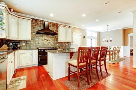 Photo pour Cuisine de luxe blanche avec cerisier feuillus et îlot avec chaises . - image libre de droit