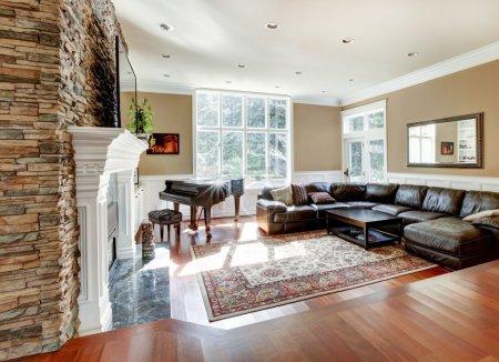 Photo pour Lumineux salon de luxe avec cheminée en pierre et bois de cerisier avec canapés en cuir . - image libre de droit