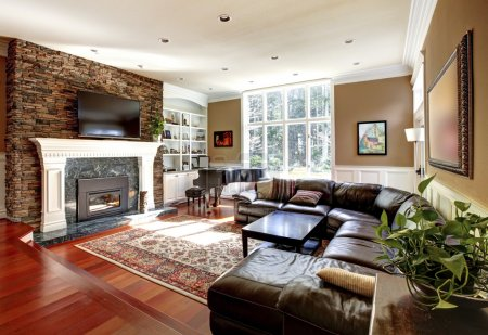 Photo for Luxury living room with stobe fireplace and leather sofas, cherry hardwood and nice rug. - Royalty Free Image