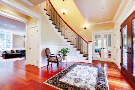 Photo pour Entrée de maison de luxe avec plancher en bois de cerisier et escalier . - image libre de droit