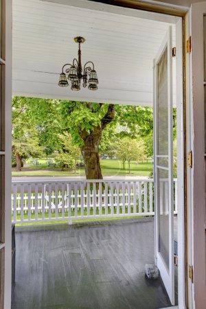 Photo pour Porte ouverte à la véranda avec vue sur le parc et la balustrade blanche. - image libre de droit